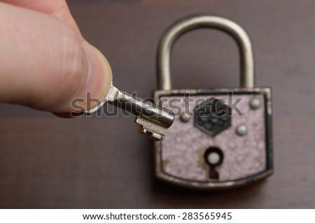 old padlock with key on dark background - stock photo