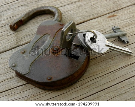 old padlock with keys on wooden background - stock photo