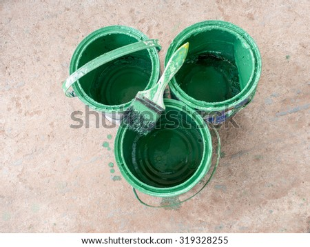 Old paint brush rest on top of green paint Bucket - stock photo