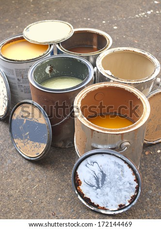 Old Paint in Messy, Rusty Cans Ready for Recycling - stock photo