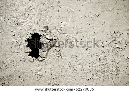 old  painted ruined surface with a black hole - stock photo