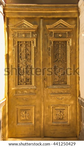 Old painted wood doors texture, grunge background, cracked paint. Gold paint on wood. Vintage retro street door with ornaments. Elaborately carved pattern on the wooden door. - stock photo