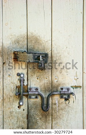 old painted wooden dirty door with rusted lock and hasp