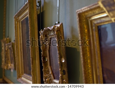 Old paintings in golden frames - stock photo