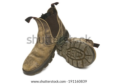 Old pair of dirty working boots isolated on white background with shadow underneath.