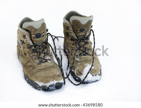 Old pairs of mountaineering boots on snow - stock photo