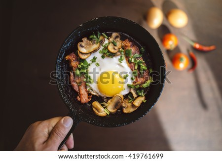 old pan in hand. fried egg, bacon, mushrooms, green onion - tasty Breakfast or snack. On a dark wooden out of focus table. Top view - stock photo