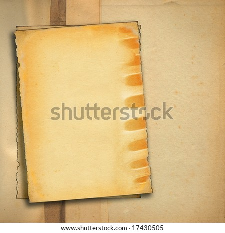 old paper against stained dirty background, edges are very frayed - stock photo