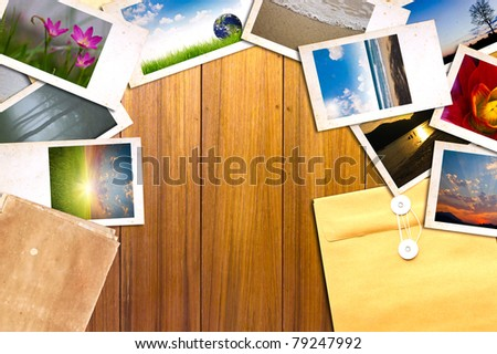 Old paper and photos on wooden table - stock photo