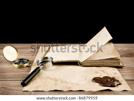 old paper, book, magnifying glass on a black background