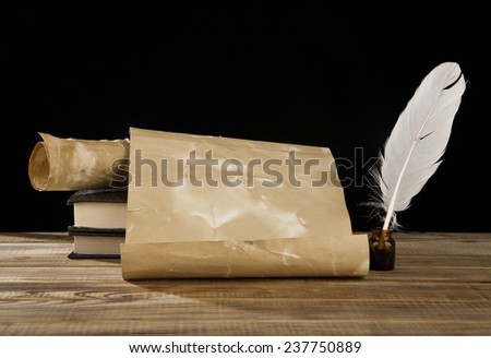 old paper, books and feather on a black background - stock photo