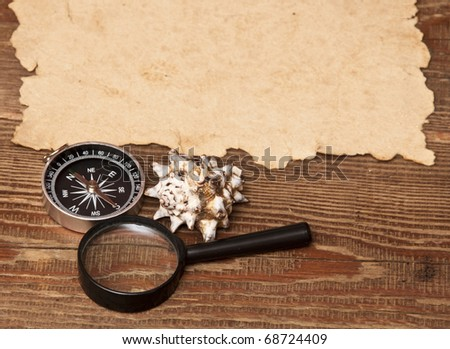 old paper, compass and magnifying glass on wood background