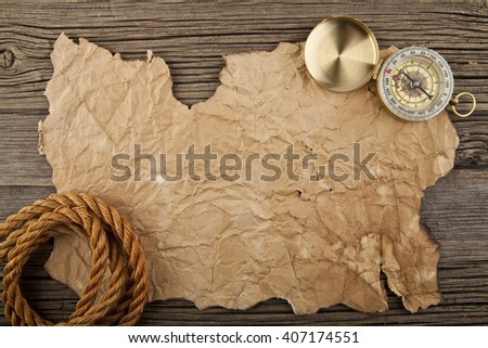 old paper, compass and rope on old wood background - stock photo
