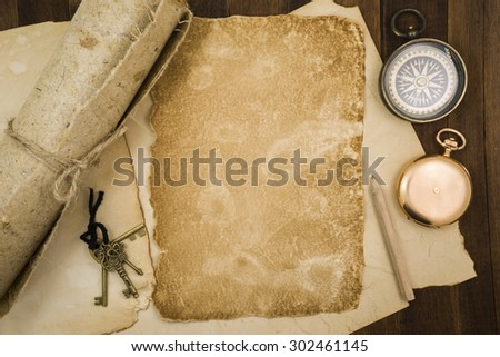 Old paper, compass, pocket watch on wooden background.
