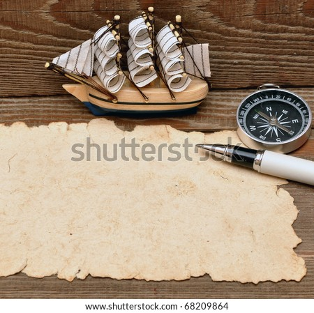 old paper, compass, rope and model classic boat on wood background - stock photo