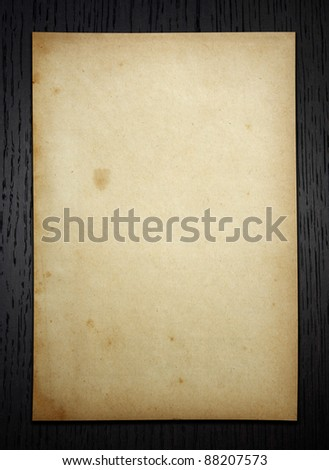 Old paper on dark wood  background with clipping path - stock photo