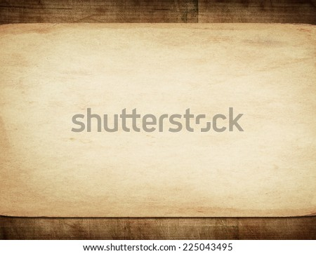 Old paper on dark wooden wall with copy space - stock photo