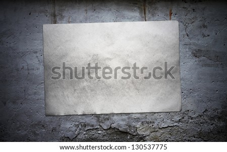 old paper on grey dirty wall - stock photo