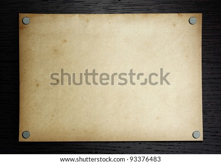 Old paper on the dark wood background - stock photo