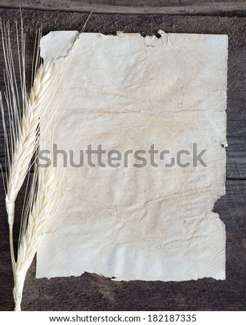 Old paper on wood background with wheat