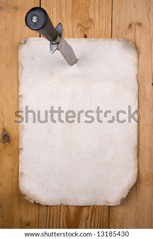 Old paper pinned to a wooden wall  with a knife - stock photo
