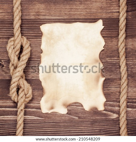 Old paper poster blank on vintage wooden wall background with rope - stock photo