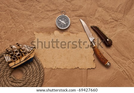 old paper, rope coil, compass, decorative knife and model classic boat - stock photo