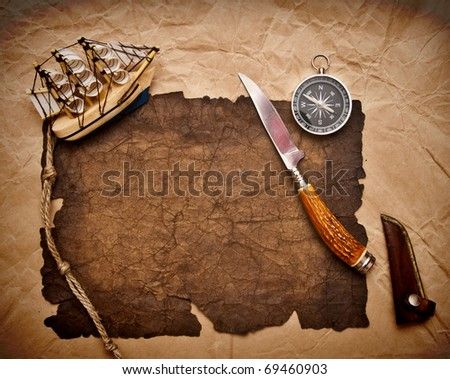 old paper, rope, compass, decorative knife and model classic boat on very old paper - stock photo