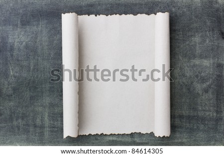 Old paper scroll on a black broad background - stock photo