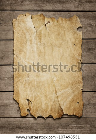 Old paper sheet nailed to a grunge wooden background with copy space - stock photo
