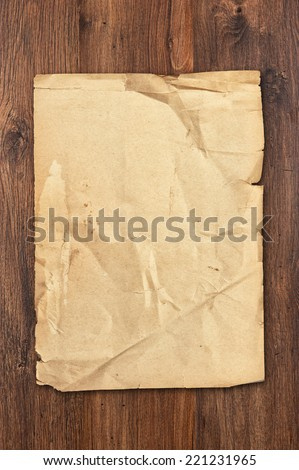 old paper sheet on brown aged wood background - stock photo