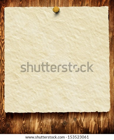 Old paper sheet on wooden background with space for your text or image - stock photo