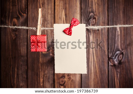 old paper sheet with bow and small gift box hanging on clothesline against wooden background - stock photo