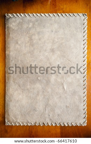Old paper texture against a deep wood background - stock photo