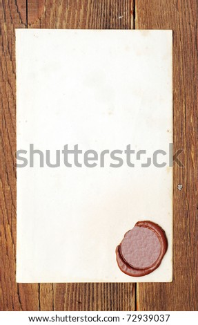 Old paper with a wax seal on a wood background - stock photo