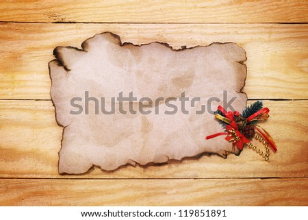 old paper with Christmas decorations on the wooden table - stock photo