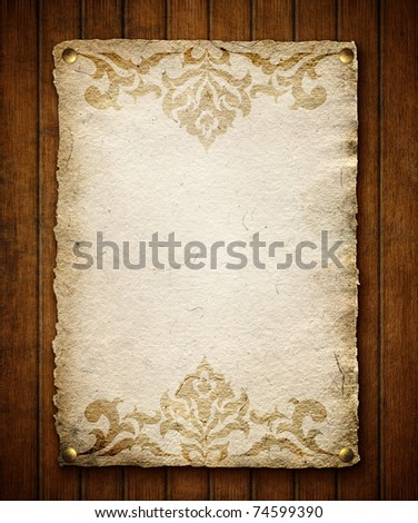 Old paper with ornament on wooden wall - stock photo