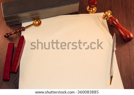 Old paper with wax seal, stamp and pen on wooden background. - stock photo