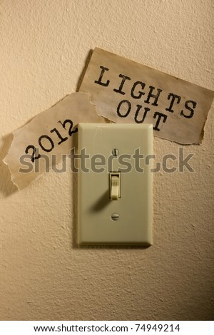 Old papers next to a light switch that say 2012 and Lights Out representing the end of the world. - stock photo