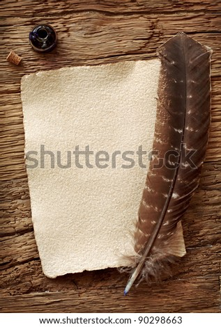 Old parchment and quill pen on wooden background - stock photo
