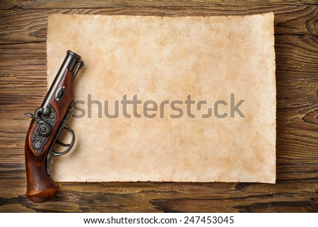 old parchment with pirate pistol on aged wooden background - stock photo