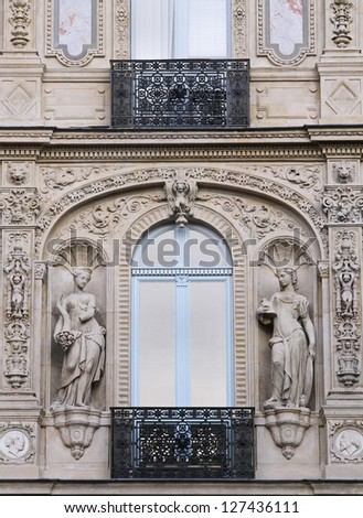 Old Paris architecture building facade with stone statues - stock photo