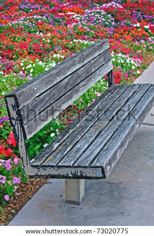 Old Park Bench in Miami, Florida with colorful flowers in the background - stock photo