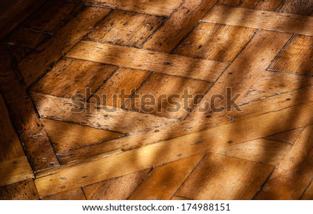 Old parquet floor in the morning light. Game of light and shadow. - stock photo