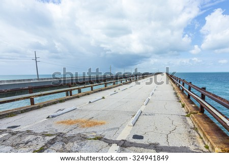 old part of the seven miles bridge under cloudy sky - stock photo