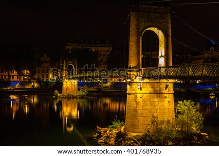 Old Passerelle du College bridge over Rhone river in Lyon, France at night