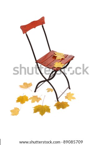 Old patio chair and  autumn leaves, isolated on white - stock photo