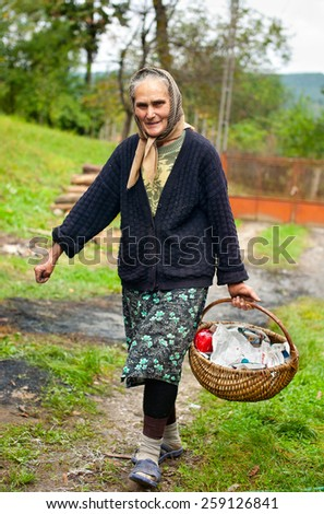Old peasant woman with basket outdoor - stock photo