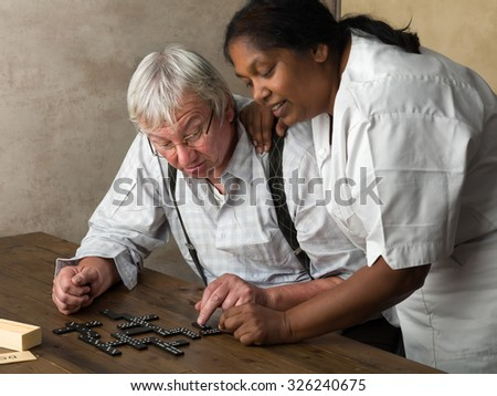 Old pensioner in nursing home playing domino - stock photo