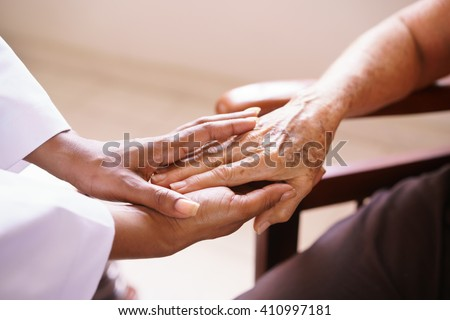 Old people in geriatric hospice: Aged patient receives the visit of a female black doctor. They shake their hands and talk in the hospital. - stock photo